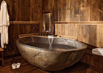 baignoire dans un bloc brute en pierre massive